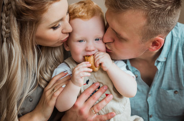 Mom and Dad kiss their son on the cheeks.