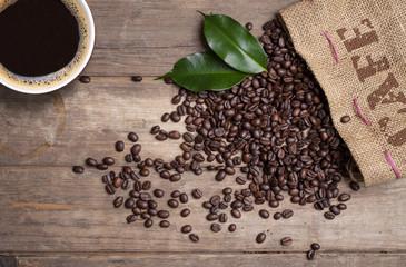 Kaffeesack mit Kaffeebohnen und Kaffeetasse auf Holzbrett