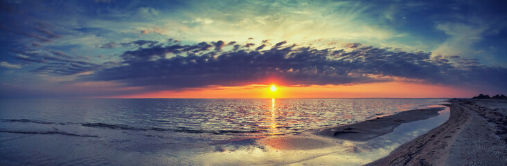 Beautiful summer sunset with reflection in the surf, panorama, banner