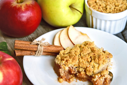 Apple crumble on with dish with spoon and fresh green and red apple with cinnamon stick on wooden floor. Easy and Basic dessert menu.
