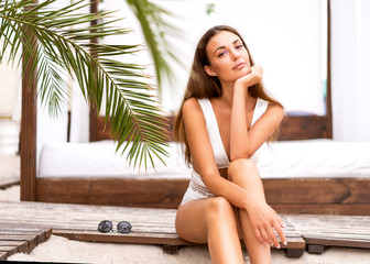 fashion girl in a swimsuit sits on the beach in tropical palms
