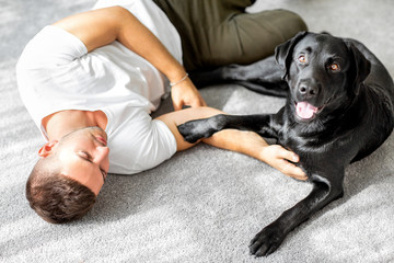 guy freelancer with his dog labrador playing at home