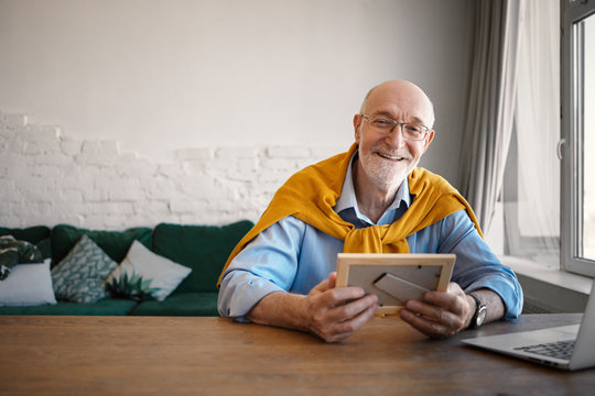 Horizontal shot of cheerful sixty year old stylish businessman wearing rectangular eyeglasses sitting in front of open portable computer, holding family portrait in photo frame and smiling happily
