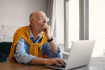Picture of attractive stylish seventy year old senior businessman wearing eyeglasses and formal clothes having thoughtful pensive look while working on laptop pc, sitting at desk by window