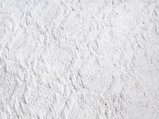 Texture of hand-woven white fabric. Rough threads, prominent textile pattern.