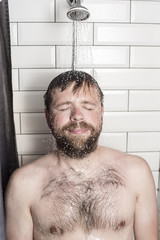 Cute bearded man standing in the shower under running water and smiles happily.
