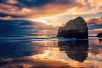 beautiful stunning magical ocean landscape, coast of Portugal, the Algarve at sunset, clouds reflected on the sand