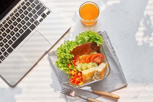 Top view of laptop, orange juice in glass and fresh salad in lunch box  at workplace