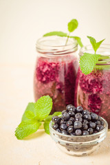 Blueberry smoothie decorated with fresh green mint leaves and raw ripe berries on yellow pastel background.