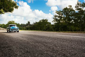 Old american classical car in highway road of Cuba