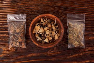 Dry psilocybin magic mushrooms and marijuana buds in plastic bags.