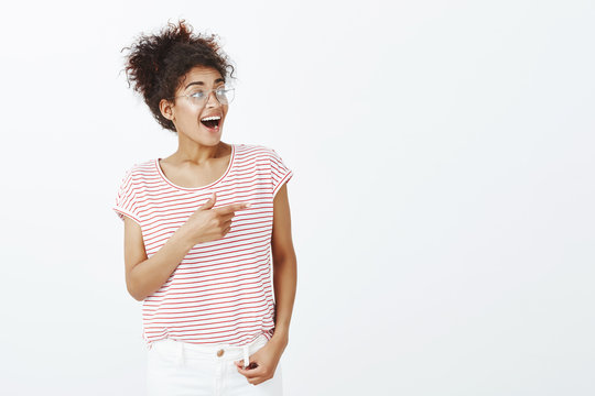 Indoor shot of impressed outgoing attractive woman with combed curly hair in glasses and striped t-shirt, looking and pointing right with curious and surprised expression, being happy and fascinated