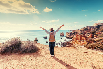 Fototapete - Beautiful young woman traveler stands on a rock above the ocean with raised hands in the Algarve, Portugal