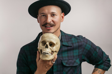 Creative painter holding human skull in hand and looking at camera over studio white background