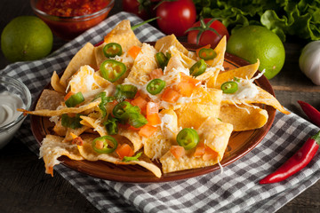 Mexican nachos with tortilla, hot pepper, melted cheese, ketchup and white sauce, jalapeno and lime on wooden background. Fast food and junk food concept. Chili con carne.