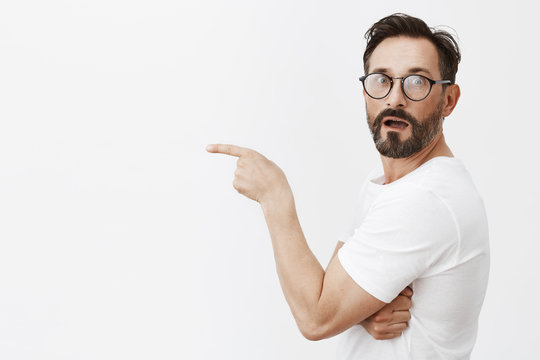 Wow, it is masterpiece. Portrait of charmed and impressed good-looking mature male in glasses and t-shirt, standing in profile, turning to camera to express amazement, pointing left with index finger