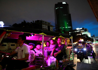 A family sit in a Tok Tok as they are stuck in the traffic in Bangkok