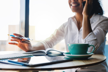 Smiling business woman talking on mobile phone while sitting in cafe at window