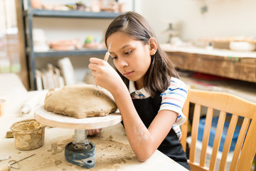Student Carving Floral Pattern On Clay During Pottery Class