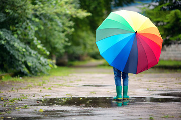 Child walking in wellies in puddle on rainy weather. Boy holding colourful umbrella under rain in summer