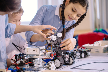 Excited little kid and two smiling teen friends construct robotic toys while playing during their...