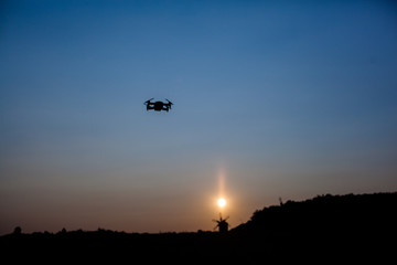 Flying drone in the background of a sunset in the backlight.