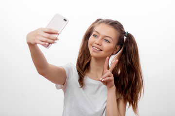 positive hipster girl wearing two ponytails showing victory sign while taking selfie, isolated white background, sign, gesture, happiness concepts