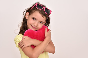 Portrait of a smiling cute young girl hugging plush red heart