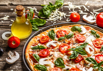 Fresh pizza with tomatoes, cheese and mushrooms