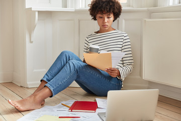 Indoor shot of pleasant looking black businesswoman has paper work at home, dressed in casul striped sweater and jeans, uses laptop computer for checking information, enjoys domestic atmosphere