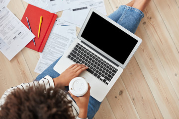 Cropped shot of dark skinned freelancer with Afro haircut, works on laptop computer, keyboards, surrounded with business papers, drinks coffe, sits on floor at home. Female student studies indoor