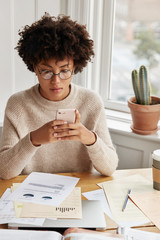 Busy businesswoman with Afro hairstyle, works with documentation, checks bank account via cell phone, dressed in oversized warm sweater, sits near window in cozy room. Time for work. Technology