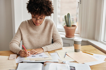 Clever busy young woman accountant with curly dark hair, dressed casually, works on financial report at home, writes graphics and schemes, sits at desktop with coffee, documetns and cell phone