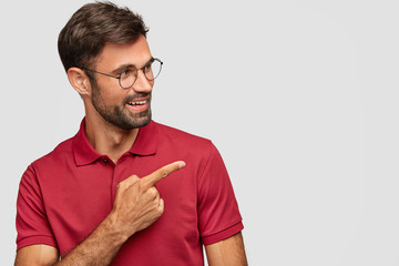 Try that direction. Cheerful unshaven guy wears spectacles, shows way, points aside, has happy satisfied expression, wears red t shirt, isolated over white background, demonstrates free space