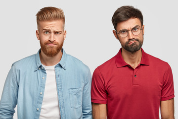 Discontent hipsters frown faces, look in bewilderment, have displeased facial expressions while hear something negative. Bearded ginger stylish man and his companion react on their duties on work