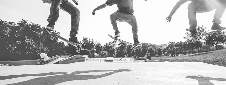 Skaters jumping with skateboard in city park