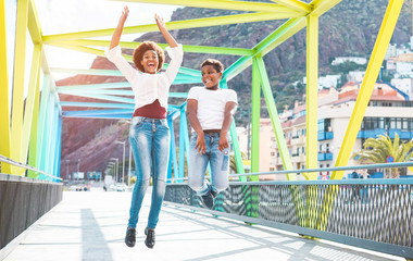Happy mother and son jumping on colorful bridge on sunny day