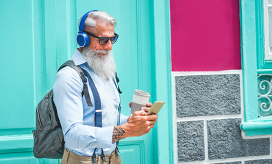 Trendy senior man using music smartphone app and drinking coffee in downtown center outdoor