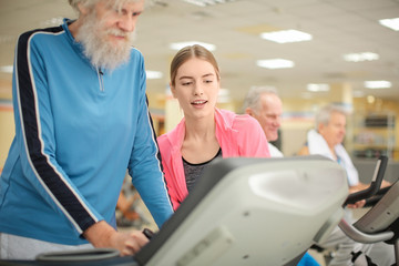 Young coach with elderly man training in modern gym