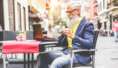 Senior businessman using laptop in bar cafeteria outdoor