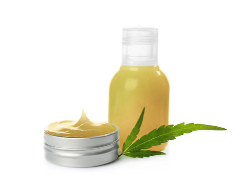 Bottle and jar with hemp lotion on white background