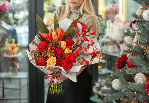Female florist holding beautiful bouquet in flower shop