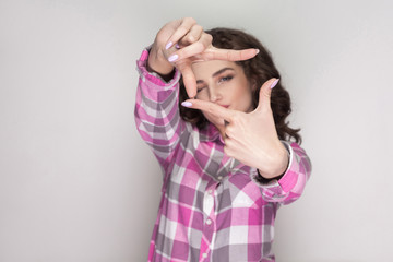 Beautiful girl with pink checkered shirt, curly hairstyle and makeup standing and looking at camera and showing cropping composition gesture. indoor studio shot, isolated on gray background.