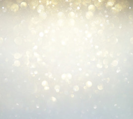 glitter vintage lights background. silver, gold and white. de-focused.