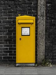 Gelber Postkasten vor einer Mauer