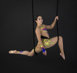 A young girl performs the acrobatic elements in the air trapeze.
