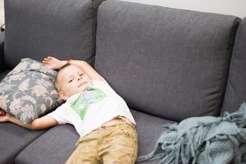 a boy of five lies on a gray sofa