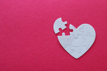 Top view image of paper white heart puzzle with missing piece over pink background. Health care, donate, world heart day and world health day concept.