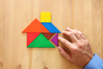 man's hand pointing at house made from tangram puzzle over wooden table.
