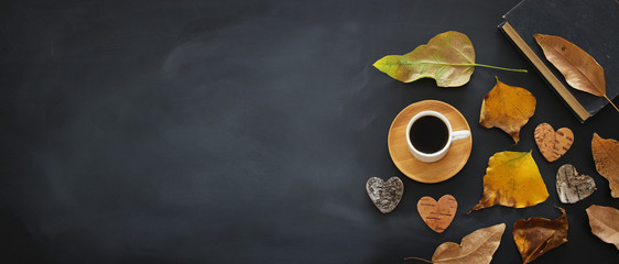 top view banner of coffee cup over blackboard background and dry autumn leaves.
